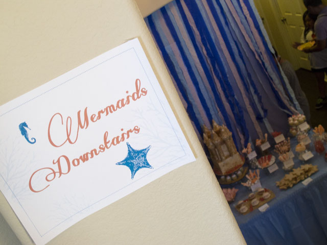 under the sea party sign and dessert table